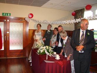 Het bruidspaar samen met de ouders achter de tafel